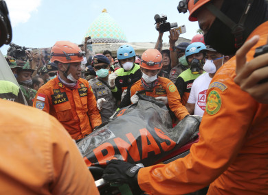 Emergency workers recover a body from the Jamiul Jamaah Mosque