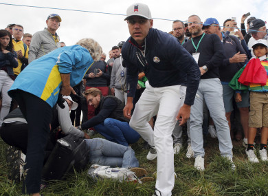 Brooks Koepka offers help to a spectator injured when his ball hit her on the 6th hole.