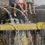 Young people sit in a fountain at the Exhibition Center in Moscow. (AP Photo / IgorYakunin)