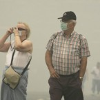 Tourists wear protective face masks as they walk along the Red Square. <span class=