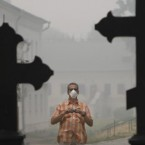 A tourist wearing a protective face mask takes photographs at the Novodevichy Monastery, as a blanket of heavy smog covers Moscow, Russia, Friday, Aug. 6, 2010. The city of Moscow was shrouded Friday by a dense smog that grounded flights at international airports and seeped into homes and offices, as wildfires that have killed 50 people nationwide continued to burn.<span class=