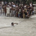 A Pakistani crosses a canal with the help of cable wire on a damaged bridge, which was washed away by heave flood in Ghazi Gat near Muzaffargarh, in central Pakistan on Monday, Aug. 9, 2010. (AP Photo/K.M. Chaudary)