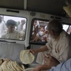 Pakistani flood affected people get relief food in Nowshera, northwest Pakistan. (AP Photo/Mohammad Sajjad)