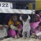 Pakistani villagers wait for transport to flee their homes due to heavy flooding in Muzaffargarh, in central Pakistan. (AP Photo/K.M. Chaudary)