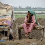 A Pakistani flood affected woman sits on the bed as she with her family members take shelter on higher ground due to flooding in an area of Jaffarabad, Pakistan. (AP Photo/Fida Hussain)