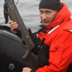 Putin holds a crossbow as he sits on a rubber boat at the Olga Harbor during a scientific expedition, to study gray whales last week. Any sensible whale in the locale legged it. (Alexei Druzhinin/AP/Press Association Images)<span class=