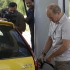No, wait! He's just a regular guy! Putin fills the tank of a yellow Russian-made Lada Kalina at petrol station on the newly-opened Chita-Khabarovsk highway on Friday. (AP Photo/ RIA Novosti, Alexei Druzhinin, pool)<span class=