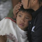 A villager comforts her son at a temporary shelter as they flee from erupting Mount Sinabung in Karo, North Sumatra, Indonesia, Sunday, 29 August, 2010. (AP Photo/Binsar Bakkara)<span class=