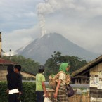 Villagers watch as Mount Sinabung spews volcanic materials in Karo, North Sumatra, Indonesia, Monday, 30 August, 2010. (AP Photo/Binsar Bakkara)<span class=