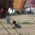 A displaced Pakistani child plays at a camp for flood-affected people in Razzakabad on the outskirts of Karachi. (AP Photo/Fareed Khan)