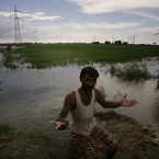 Local farmer Abdul Razzaq gestures standing in his field submerged in a flood water in Shikarpur, Pakistan on Monday, Aug. 16, 2010. The river that for generations was a lifeline turned destroyer, ripping up rice, wheat and sugar cane crops and leaving bloated corpses of cow and goats in its wake. When the waters recede, millions of farmers who used the Indus to irrigate their crops _ and propel Pakistan's economy _ face an uncertain future.(AP Photo/Shakil Adil)
