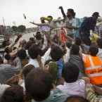 Pakistani displaced by flooding reach for food aid given by volunteer along main road near Marli, Sindh province, southern Pakistan, Wednesday, Sept 1, 2010. (AP Photo/Vincent Thian)<span class=