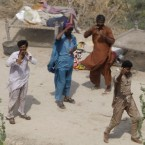 A family waiting for Army helicopter to drop relief at a flooded area in the southern city of Thatta, Sindh province, southern Pakistan, 1 September, 2010. (AP Photo/Vincent Thian)<span class=