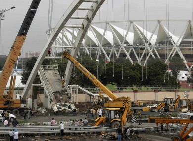 Construction workers clear the damage after a footbridge collapsed outside the main Commonwealth Games stadium yesterday.
