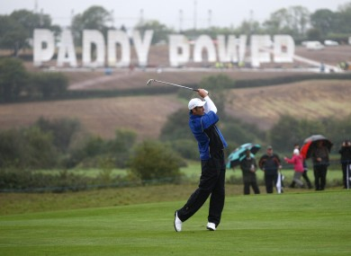 Europe's Ross Fisher tees off in a practice round yesterday - within clear view of the 270ft sign in a nearby field.
