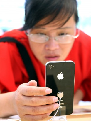 A Chinese buyer examines a display iPhone 4 in Shanghai. The white edition of the handset has been delayed yet again.