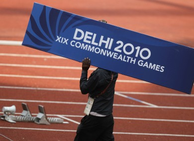 A worker carries a Delhi 2010 signboard across the track in preparations for the track and field event of the Commonwealth Games at the Jawaharlal Nehru Stadium