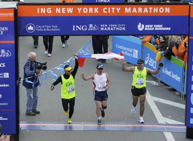 Edison Peña, flanked by two assistant runners, finishes the New York City Marathon to rapturous applause.