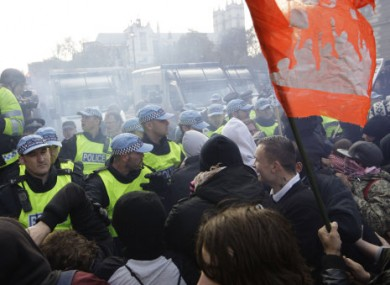 Protesters clash with police over tuition fee hikes at Whitehall, London, today.