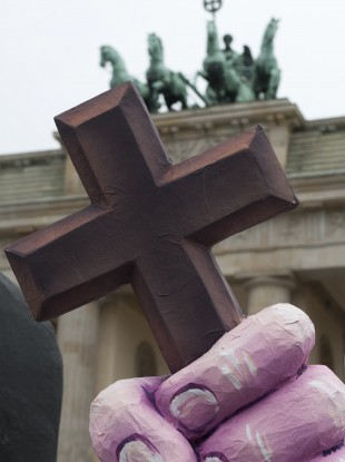 The hand of a character symbolising a nun holds a cross in front of the Brandenburg Gate during a demonstration against church abuse in Berlin earlier this year.