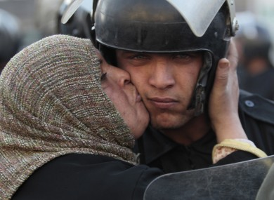 An Egyptian anti-government activist kisses a riot police officer following clashes in Cairo yesterday.