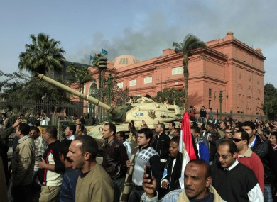The Egyptian Museum in downtown Cairo is guarded by an army tank. The smoke seen behind is coming from the headquarters of President Mubarak's National Democratic Party.
