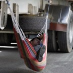 A truck driver sleeps in a hammock under his truck during a strike in Bogota, Colombia to protest high fuel prices and low pay. (AP Photo/Fernando Vergara)