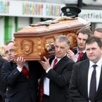 The coffin of PSNI Constable Ronan Kerr is carried through his home town of Beragh in Co Tyrone, to the Church of the Immaculate Conception by members of the Red Knights GAA club.