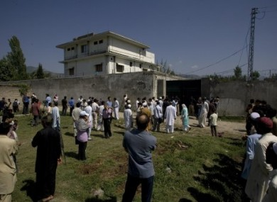 Local people and media gather outside the wall of the compound and house where bin Laden was killed.
