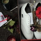 Candles and a red flower are seen beside golf shoes during the funeral service.<span class=