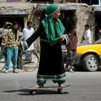 An Afghan girl skateboards down a street to mark Go Skateboarding Day in Kabul (AP Photo/Ahmad Nazar)