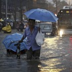 A Chinese man pulls his tricycle on a flooded road during a heavy rain storm in Beijing, China (AP Photo/Color China Photo)
