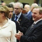 Enda Kenny enjoys a joke with Angela Merkel at the EU summit in Brussels - but Nicolas Sarkozy doesn't look impressed (AP Photo/Geert Vanden Wijngaert)