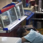 A vendor takes a nap as he waits for customers at a food store in Beijing, China (AP Photo/Andy Wong)