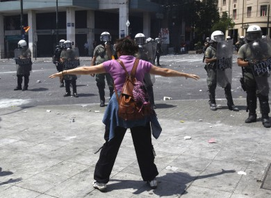 A woman demonstrator faces police during a demo in Athens