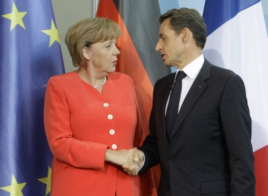 Merkel and Sarkozy shake hands after finding common ground at a meeting in Berlin today