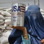 A woman carries an oil tin donated by the World Food Program in Kabul, Afghanistan. (AP Photo/Ahmad Nazar)