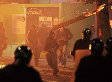 A rioter throws a burning wooden plank at police in Tottenham during Saturday night's riots. Further violence broke out in other areas of London last night.