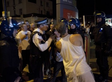 Police scuffle with men who say they are protecting their homes in Enfield, London, on Tuesday night.