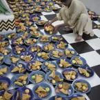 A volunteer arranges plates for people gathered to break their fast during Ramadan in Rawalpindi, Pakistan (AP Photo/B.K.Bangash)