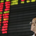 An investor covers his mouth as he looks at the stock price monitor in Shanghai, China (AP Photo)