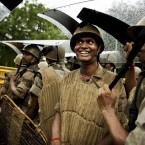 Police officers use riot shields to shelter themselves during a rain shower at a protest in New Delhi, India (AP Photo/Kevin Frayer)