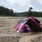 A passenger bus lies half buried in rubble after heavy rainfall on the outskirts of Jammu, India (AP Photo/Channi Anand)