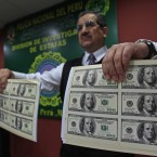 A police officer presents a sample of the nearly two million confiscated dollars in counterfeit US$100 bills in Lima, Peru (AP Photo/Martin Mejia)