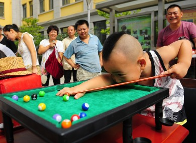 A boy plays pool during a competition exclusively for left-handed people, in Xi'an, Shaanxi Province, China.