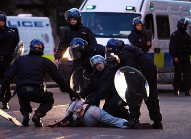 Police detain a man near the site of looting in an electronics store near New St Station, Birmingham, last night