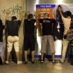 Detained demonstrators are searched by a police officer, right, after clashes at the sol square in Madrid, Spain, last night.