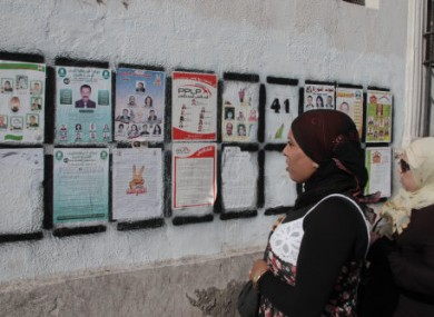 Women read election posters in Tunis.