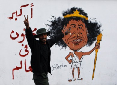 A Libyan man gestures front of a graffiti reading: