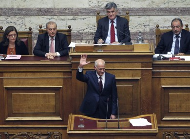 Greek Prime Minister George Papandreou waves his hand as his government's parliament members applaud after his speech in Athens